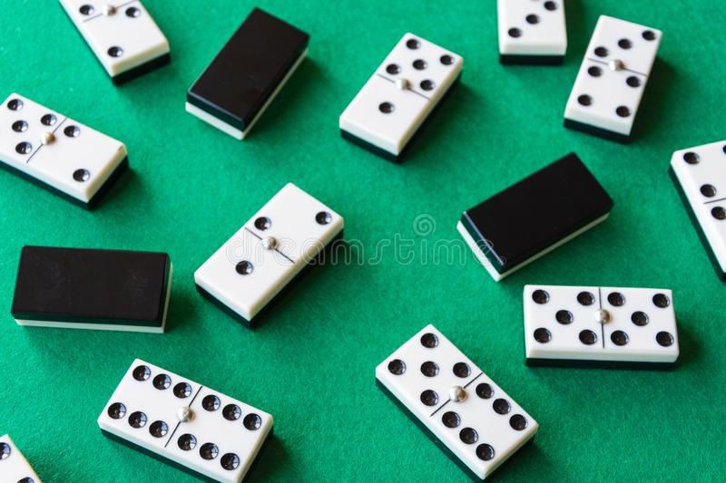 Top view of domino pieces, covered and uncovered, unfocused those in the background, on green mat to play royalty free stock photo
