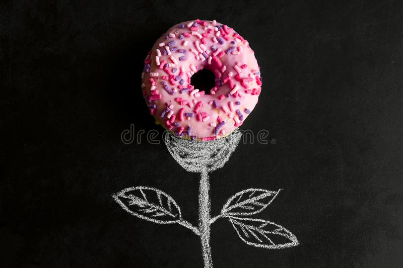 donut on chalk board with chalk drawn stem and leaves royalty free stock images