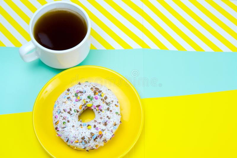 donut on a yellow plate and coffee cup  on a blue and yellow background,copy space stock image