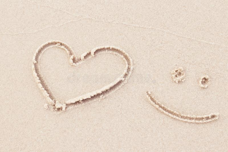 Top view of drawing heart and smile on white sand beach in background stock images