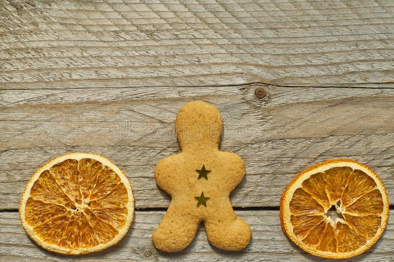 Top view of dried orange slices and ginger bread man on wooden background. Festive christmas greeting card with copy space for royalty free stock image