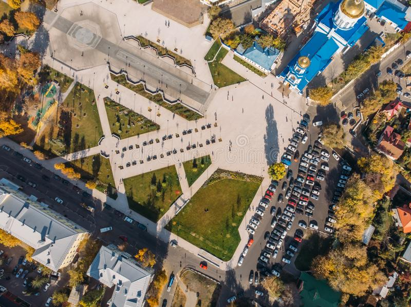 Top view from drone above park with green lawns and parking lot with cars in center of modern city, aerial shot royalty free stock photo