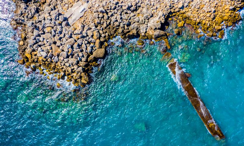 Top view from drone on the outstanding sea rocks, rocks and surf with waves. Beautiful blue water waves against rocky stock images