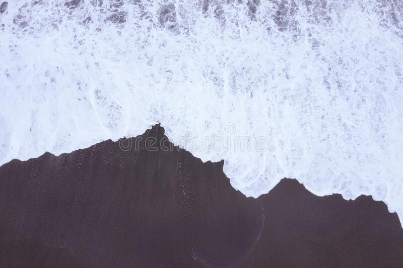 Top view from the drone on the stormy sea, white foam of waves and the beach.  royalty free stock image