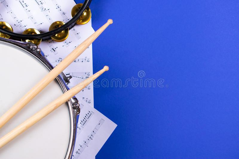 Top view of drumming equipment. Top view of drumming equipment: snare drum, tambourine, drumsticks and set of notes on blue background with copy space for text stock image