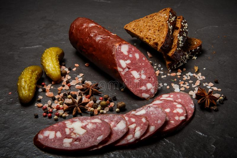 Top view of dry cured salami sausage with rye bread and pickled cucumbers stock image