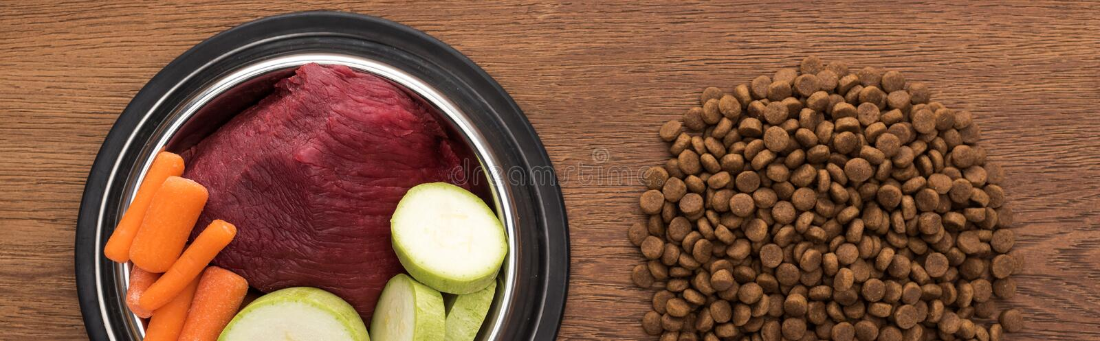 Top view of dry pet food near raw vegetables and meat in bowl on wooden table, panoramic shot. Top view of dry pet food near raw vegetables and meat in bowl on stock image