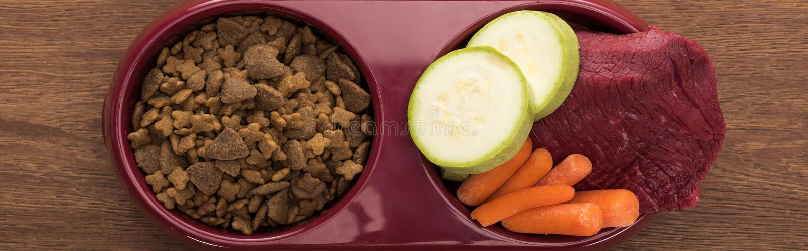 Top view of dry pet food and raw meat with vegetables in bowl on wooden table, panoramic shot. Top view of dry pet food and raw meat with vegetables in bowl on royalty free stock photo