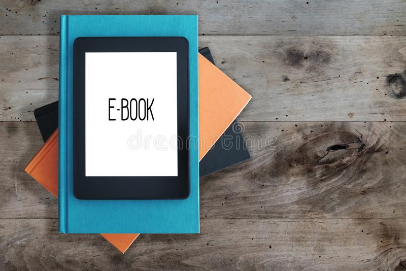 E-book reader on a stack of books on rustic wooden table concept royalty free stock photos
