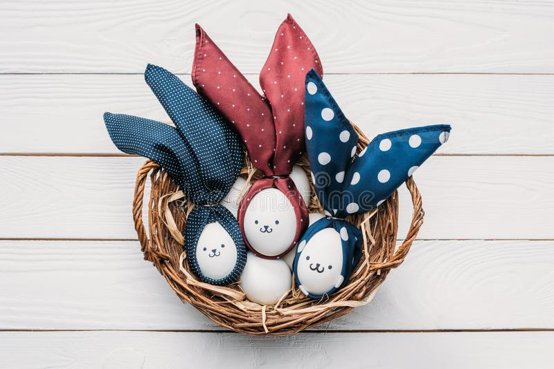 Easter chicken eggs with smileys and bunny ears in basket royalty free stock images