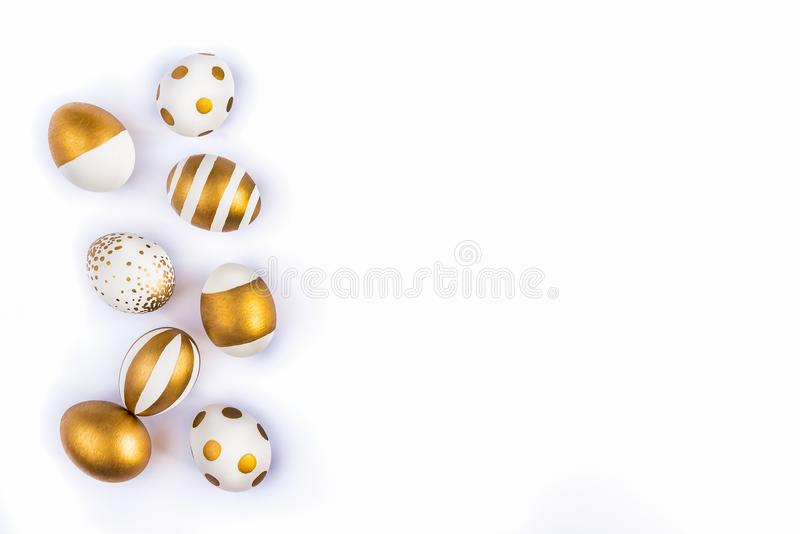 Top view of easter eggs colored with golden paint in differen patterns. Various striped and dotted designs. White background. Copy royalty free stock photo