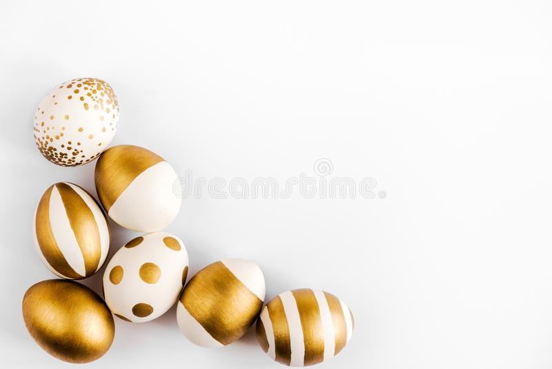 Top view of easter eggs colored with golden paint. Various striped and dotted designs. White background. stock image