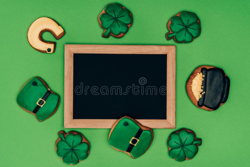 top view of empty board with icing cookies isolated on green, st patricks day concept royalty free stock photography
