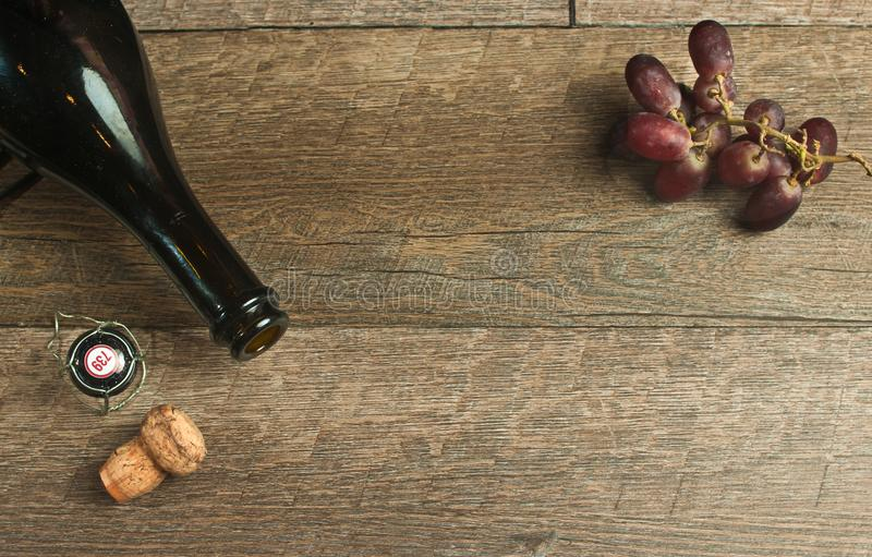 Top view of empty bottle of champaign with cork and grapes stock photography