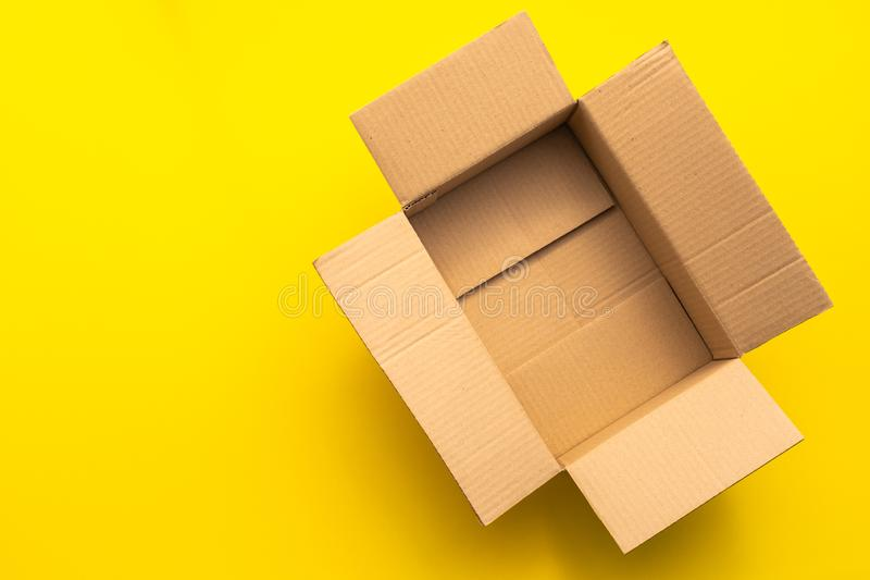 Top view empty brown post or carton box on yellow paper background. Online order and delivery concept stock photos