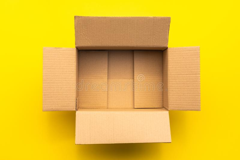 Top view empty brown post or carton box on yellow paper background. Online order and delivery concept royalty free stock image