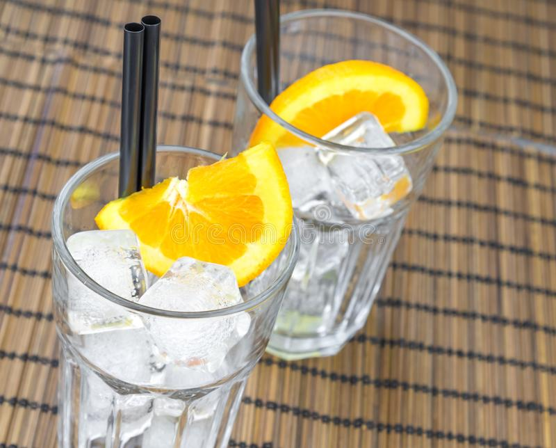 Top of view of empty cocktail glasses with two orange slices and ice cubes stock photo