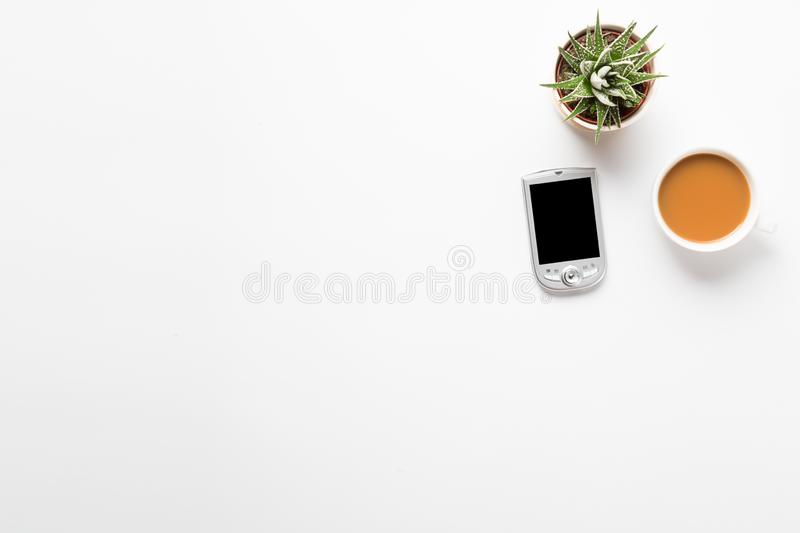 Top view of empty office desk. Green plant in a pot, cup of coffee and pocket communicator smart phone on white background. Copy. Space for your text stock photo