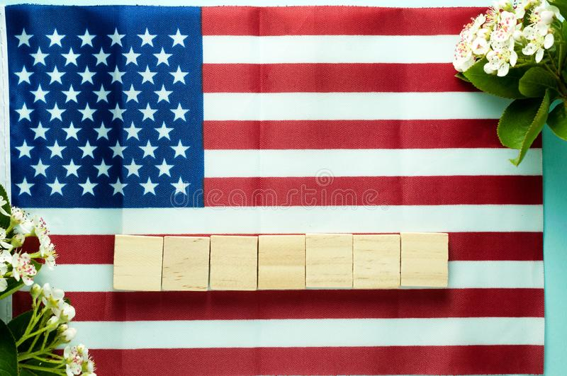 Empty seven wooden cubes laid out on American flag near blooming branches royalty free stock photography