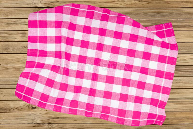 Top view of a empty violet and white checkered kitchen cloth, textile, tablecloth or napkin on blurred wooden background. Template stock image