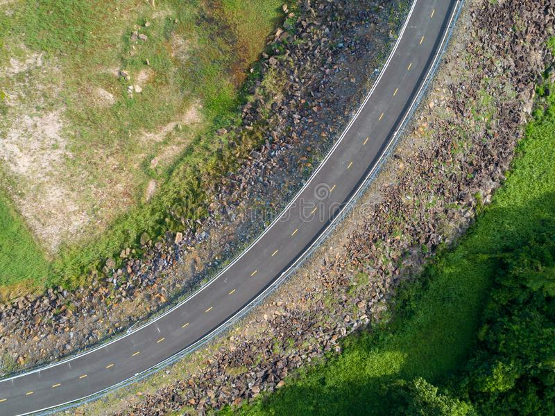 Top view an empty winding tarmac road with green trees and grass om roadside from drone aerial view. stock photo