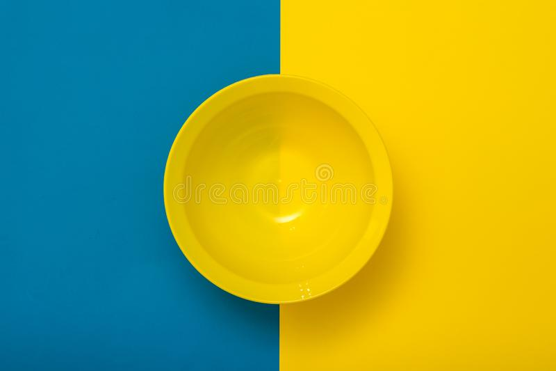 Top view of an empty yellow bowl on a yellow and blue background. royalty free stock images