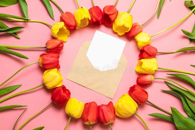 Top view of envelope and frame of red tulips on pink background stock photography