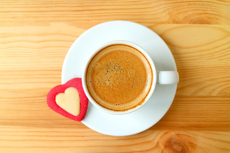 Top view of an espresso coffee with a heart shaped cookies served on wooden table royalty free stock image