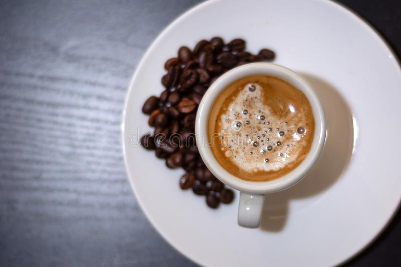 Top view of espresso coffee in a white cup and roasted coffee beans on a saucer royalty free stock photo