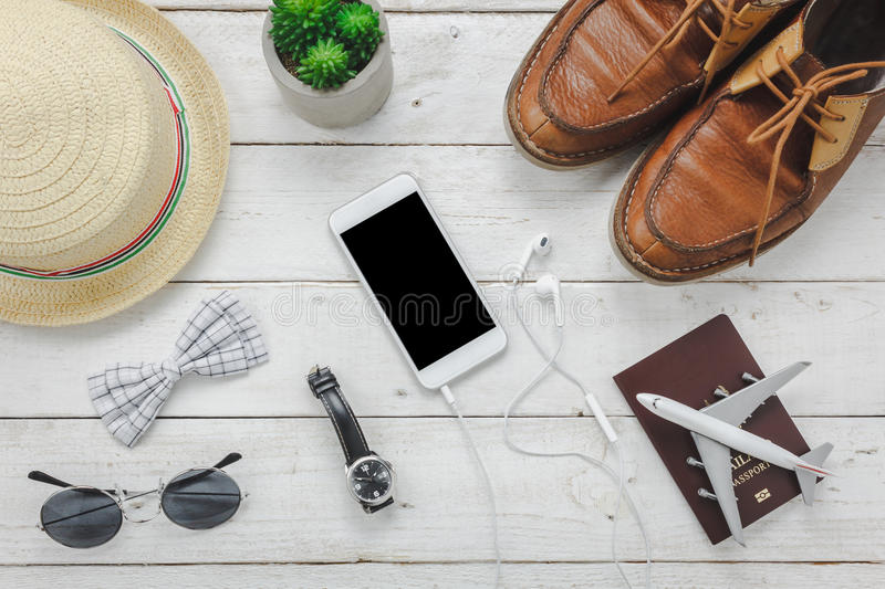 Top view / Flat lay accessoires to travel and technology with man / gentlemen clothing on white wooden table stock photo