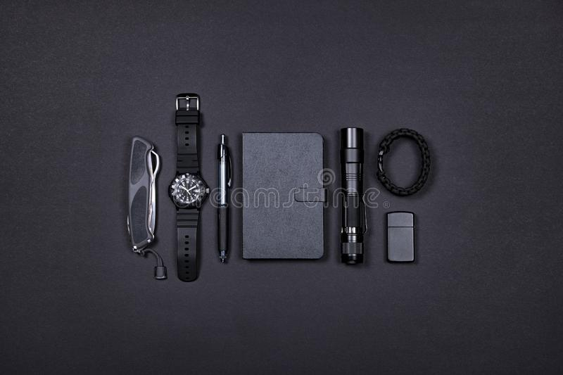 Everyday carry EDC items in black color - knife, lighter, note book, tactical pen, watch, survival bracelet and flashlight. royalty free stock photography