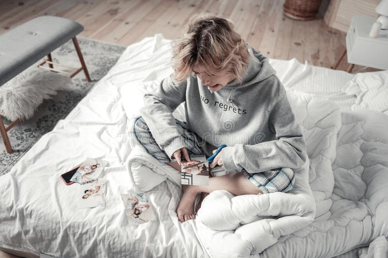 Top view of ex wife wearing pajamas sitting in bed and cutting photo. Ex wife. Top view of ex wife wearing pajamas sitting in bed and feeling emotional while stock image