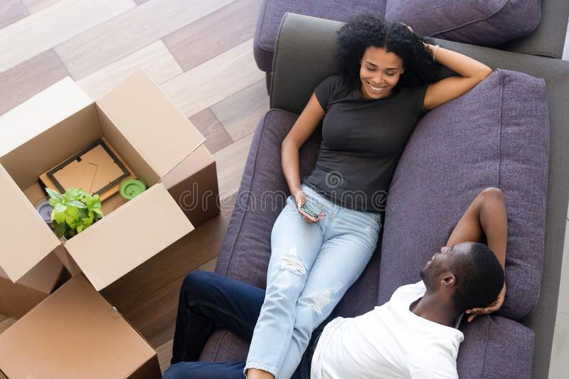 Top view excited African American couple taking break, unpack boxes royalty free stock photos