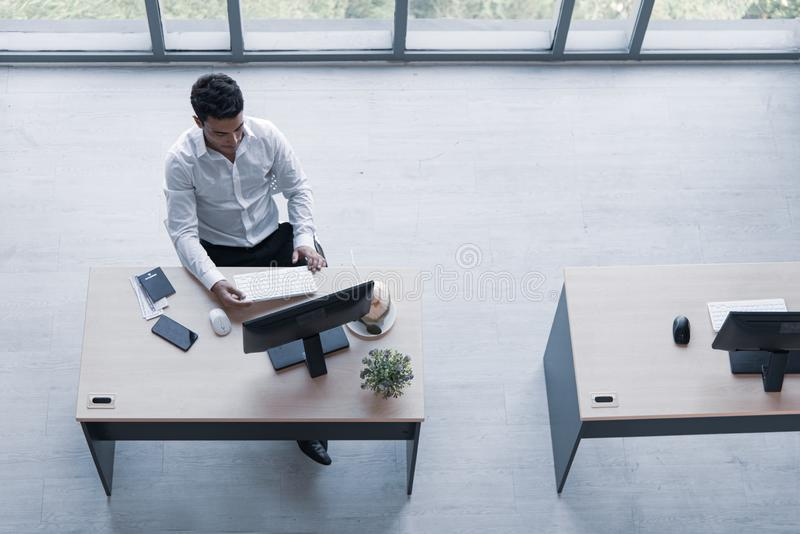 Top view of executive, manager, or engineer drinking coconut juice working on computer sitting in creative office prepare travel royalty free stock images