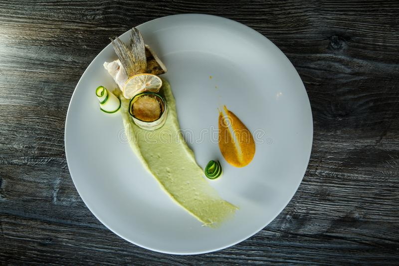 Top view on exquisite decorated fish roll with garnish on white dish. Top view on exquisite decorated fish roll with sliced zucchini and green puree garnish on royalty free stock image