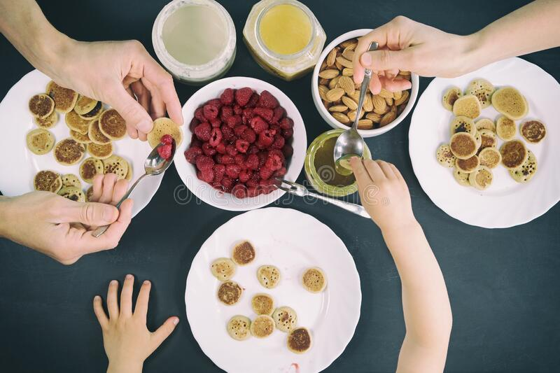 Top view family eating homemade breakfast. Tiny mini pancake cereal, sweet spreads, nuts, honey and fresh raspberries. Parents and royalty free stock photography