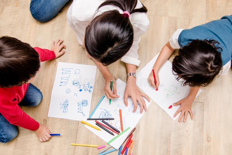 Top view Family happy children group kid boy and girl kindergarten paint drawing on peper teacher education. At interior playroom stock photography