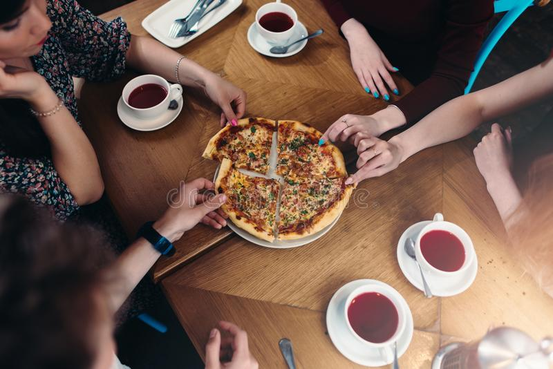 Top view of family members having lunch reaching out for pizza pieces in pizzeria royalty free stock images