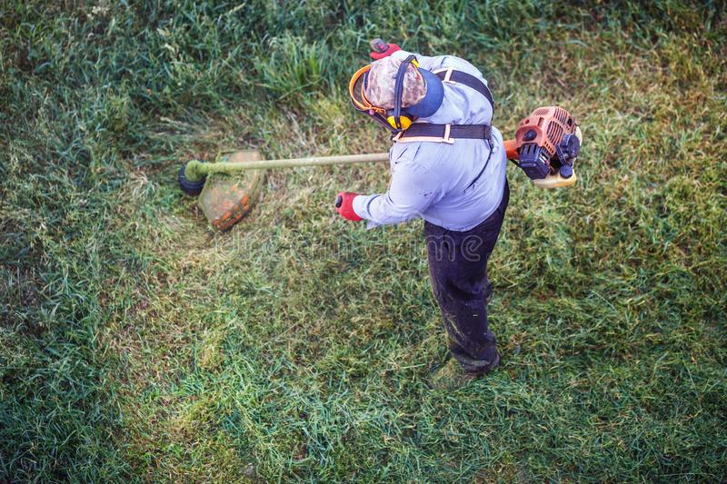 Top view fat dirty lawnmover man worker cutting dry grass with lawn mower royalty free stock photos