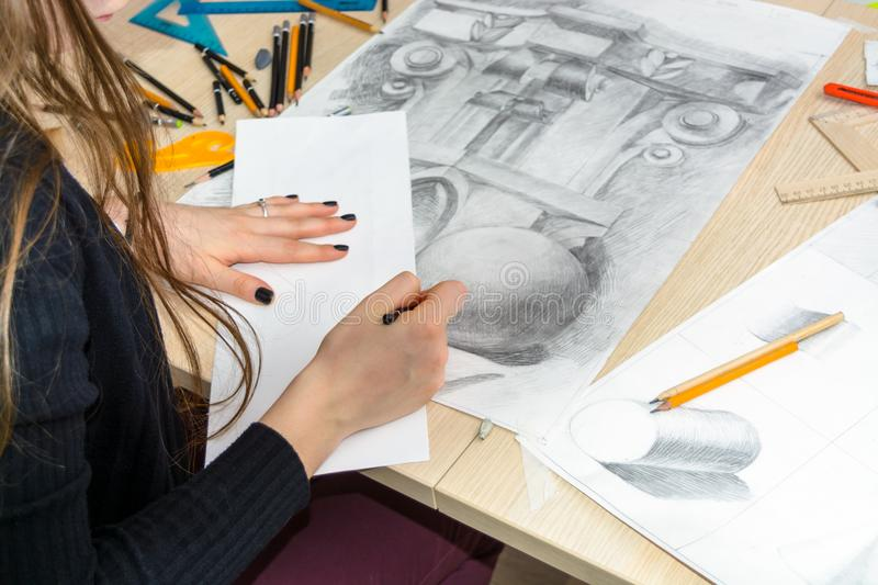 The top view of the female architect designer draws sketches in pencil on white paper. Black and white drawing of an architectural royalty free stock photos
