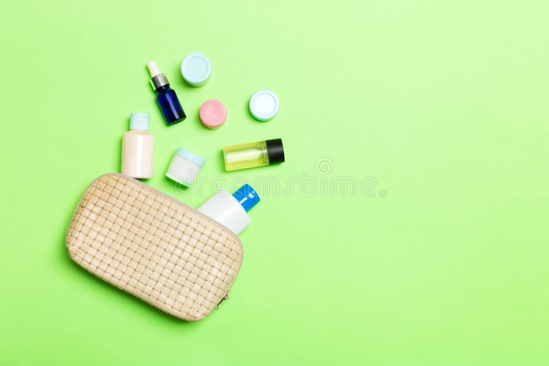 Top view of female cosmetics bag with dropped out cosmetic products on green background. Bodycare concept with copy space. Top view of female cosmetics bag with royalty free stock photo