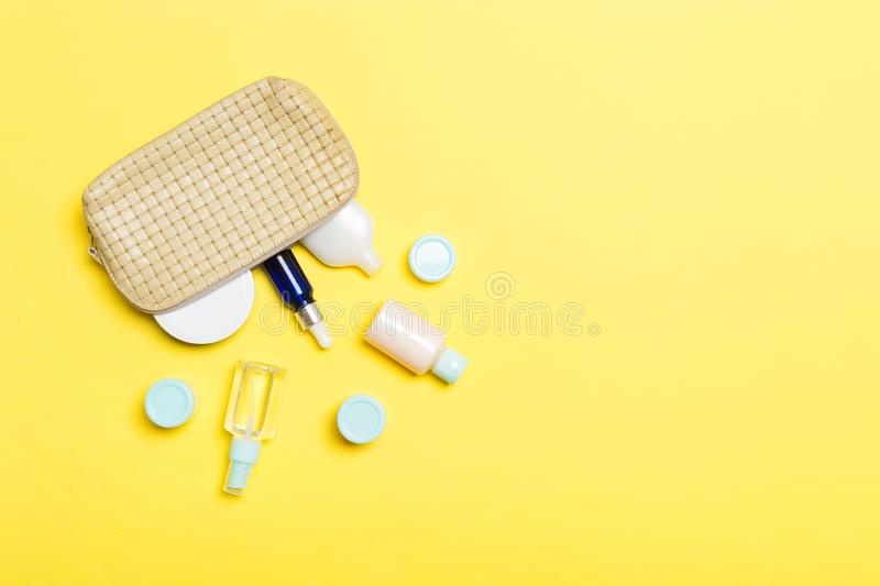Top view of female cosmetics bag with dropped out cosmetic products on yellow background. Bodycare concept with copy space. Top view of female cosmetics bag with royalty free stock photo