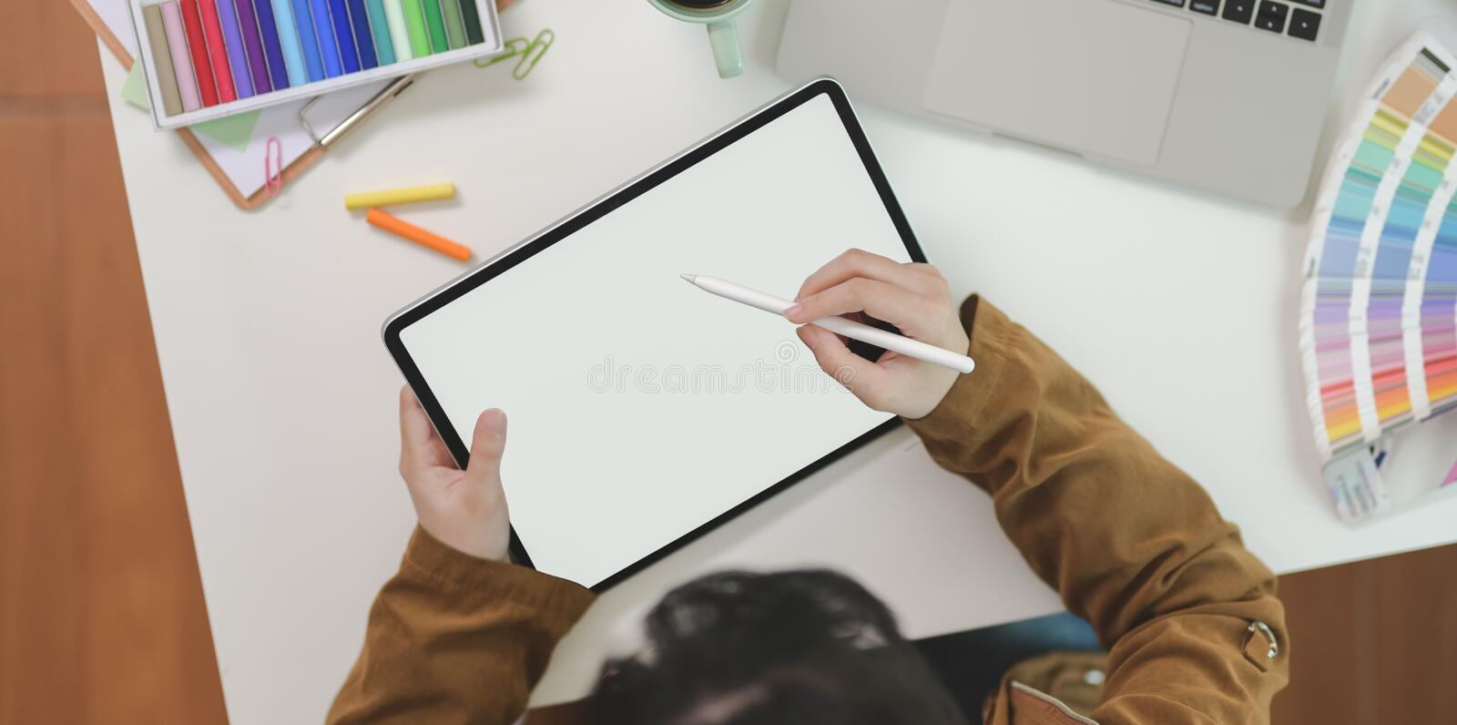 Top view of female graphic designer sketching on tablet stock images