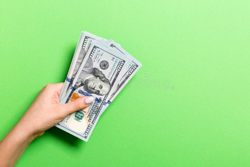 Top view of female hand giving one hundred dollar bills on colorful background. Charity and donation concept with copy space royalty free stock photo