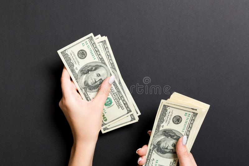 Top view of female hand giving some money, Close-up of counting one hundred dollar bills. Business concept on colorful background.  stock photography