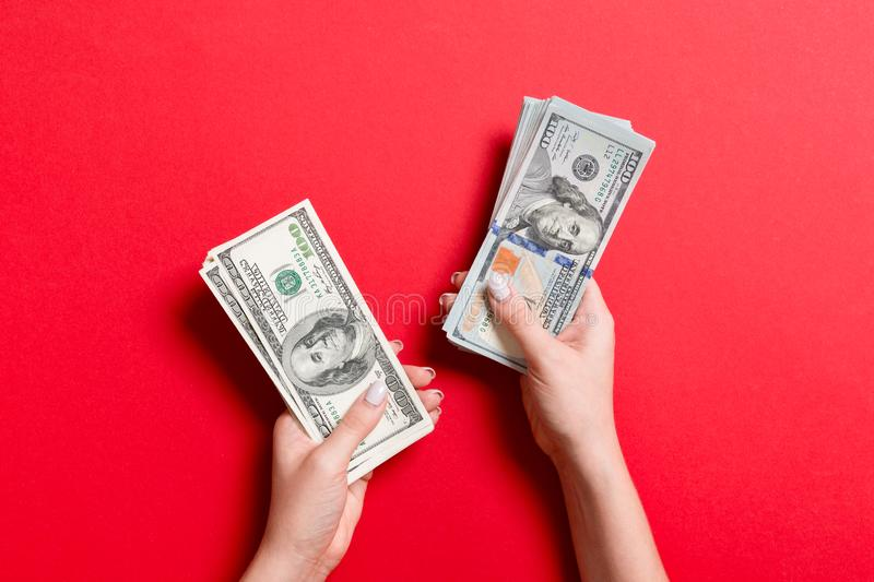 Top view of female hand giving some money, Close-up of counting one hundred dollar bills. Business concept on colorful background.  stock photo
