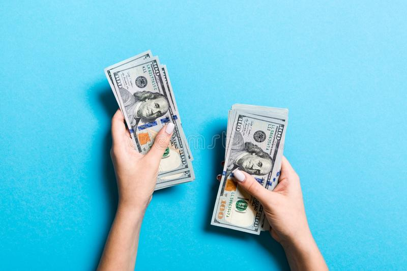 Top view of female hand giving some money, Close-up of counting one hundred dollar bills. Business concept on colorful background.  royalty free stock photography