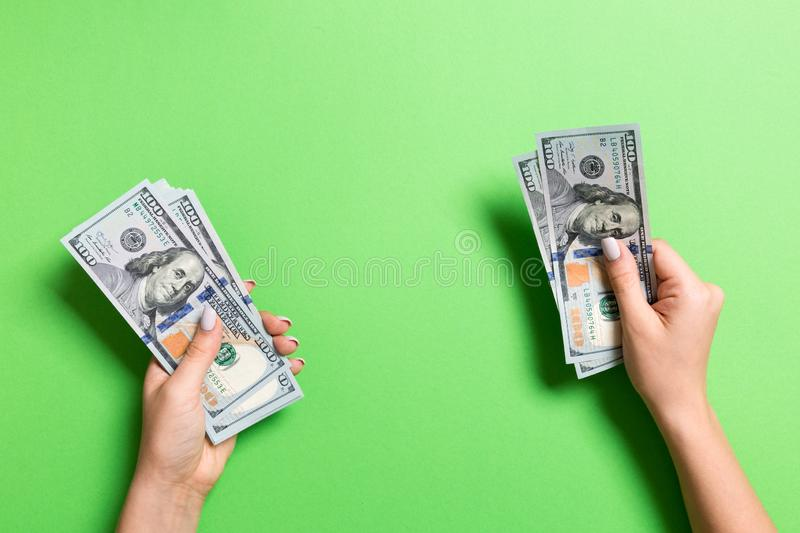 Top view of female hand giving some money, Close-up of counting one hundred dollar bills. Business concept on colorful background.  stock images