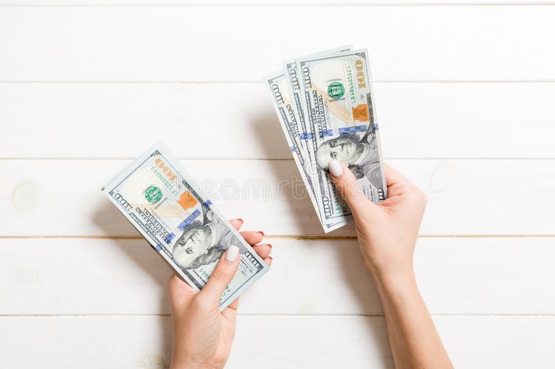 Top view of female hand giving some money, Close-up of counting one hundred dollar bills. Business concept on wooden background.  royalty free stock photos