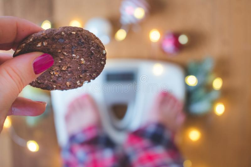 Top view of a female hand holding a cookie and scales with Christmas decorations and lights on wooden background royalty free stock photos